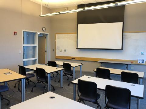 Classroom E with classroom style seating and large screen at front of room
