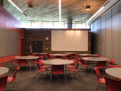 Meeting Room A at Northwest Library with round tables and a large white screen