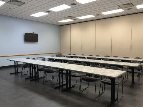 Interior image of Midwest City Meeting Room A with three rows of rectangular tables and chairs