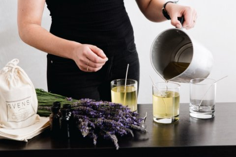 photo of a person in a black dress pouring a soy candle into a glass vessel. lavender is on the table next to the candle along with a linen pouch.