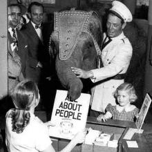 Historical image of people with a baby elephant